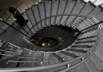 Businessman walks down the staircase of an office building in Tokyo